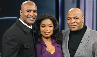 Talk-show host Oprah Winfrey poses with former world champion boxers Mike Tyson, right, and Evander Holyfield in 2009. George Burns / AP