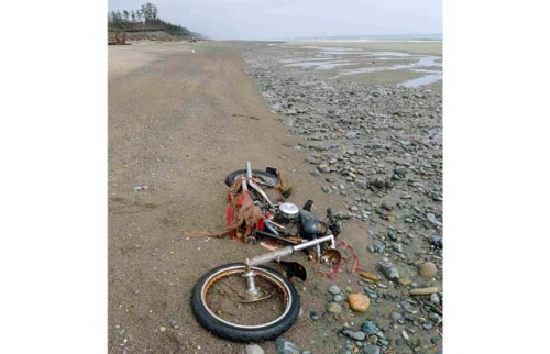 A Harley-Davidson motorcycle lies on a beach in Graham Island in this picture taken by Canadian Peter Mark in the end of April 2012 and released by Kyodo